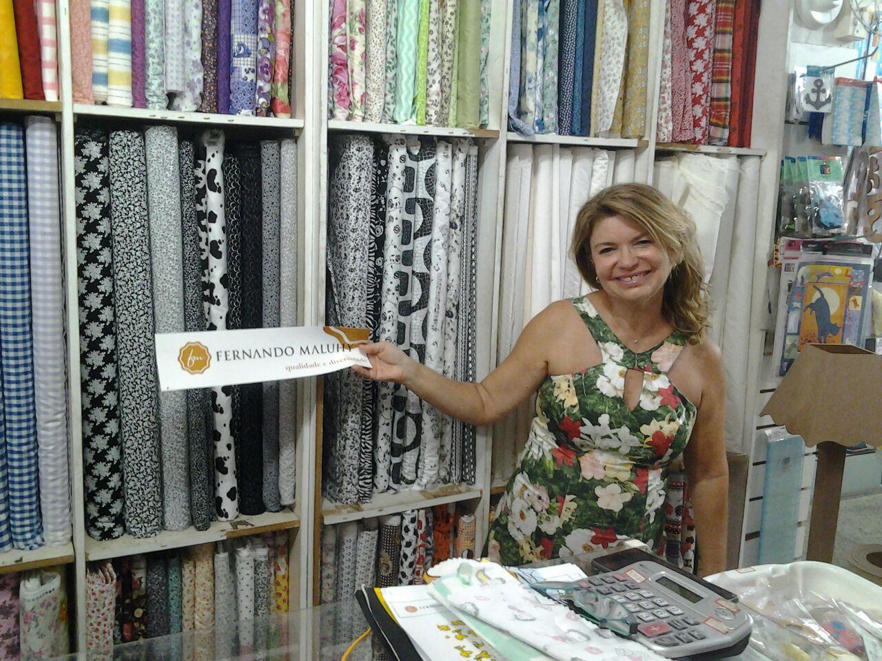 Ana Lucia, com o adesivo  Maluhy, a ser colocado na loja, Entrelinhas de Niterói
